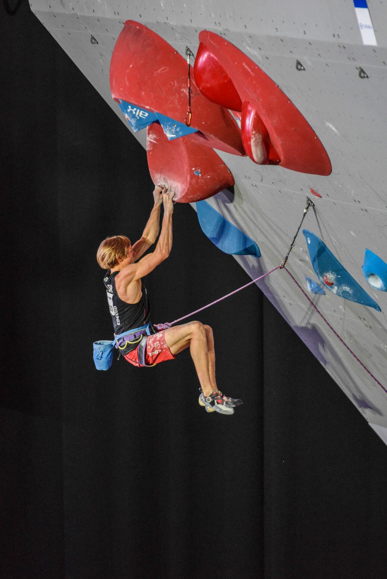 Alex Megos hängt im Überhang mit zwei Händen an einem Griff ohne Tritte